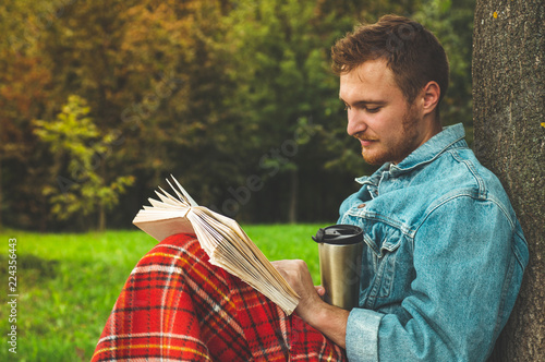 ab6920af Smiling Young Man reading book outdoor with a warm red plaid and a cup of  tea