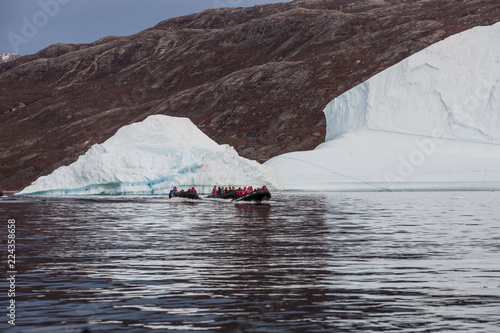 Poster Pole rubber dinghy cruising in front of massive Icebergs floating in the fjord scoresby sund, east Greenland