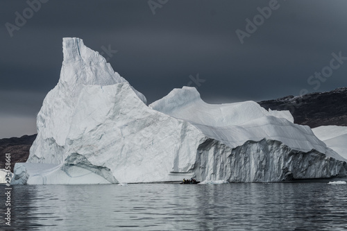 Foto op Plexiglas Arctica rubber dinghy cruising in front of massive Icebergs floating in the fjord scoresby sund, east Greenland