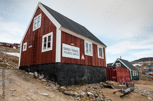 Photo Stands Pole tourist office of Ittoqqortoormiit with colorful houses, eastern Greenland at the entrance to the Scoresby Sound fjords