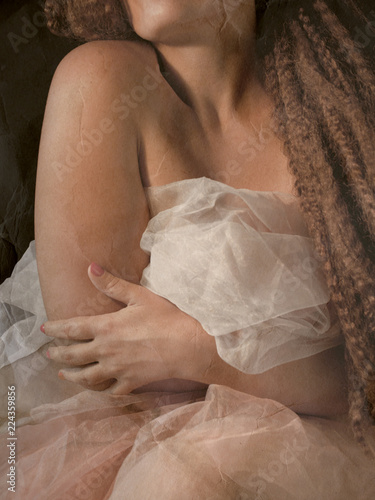 Photo lady sitting in a dark bedroom with tulle petticoat