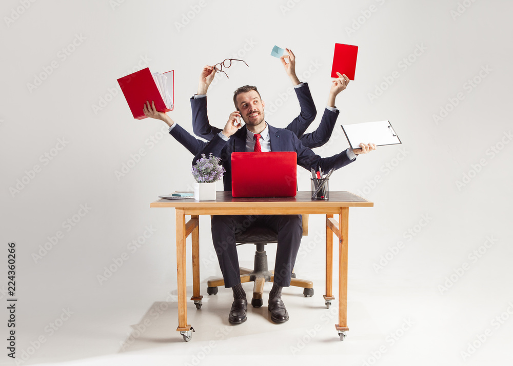Fototapeta businessman with many hands in elegant suit working and holding office tools. Isolated over white background. Concept of busy