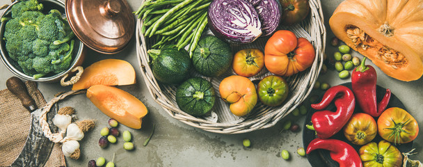 Healthy vegetarian seasonal Fall food cooking background. Flat-lay of Autumn vegetables over grey concrete background, top view, copy space, wide composition. Vegan, alkaline diet food