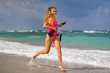Beautiful sexy girl in a swimsuit with a carbine runs along the seashore