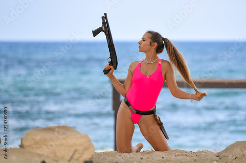 Beautiful sexy girl in a swimsuit with a carbine stands on the ruins of an ancie Fototapeta