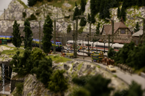 A model train and toy people are seen at a train station of