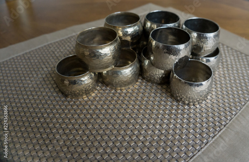 Silver metal napkin rings holders over a golden color place mat. Ready for table setting in an event, party or holiday