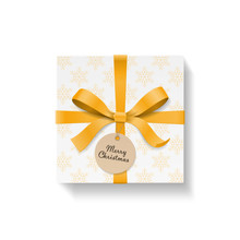 Square Gift Box, Gold Color Bow Knot And Ribbon With Circle Kraft Hang Tag. Yellow Snowflake Pattern Paper. Merry Christmas Text On Ball. Happy New Year Package. Vector Illustration 3d Top View