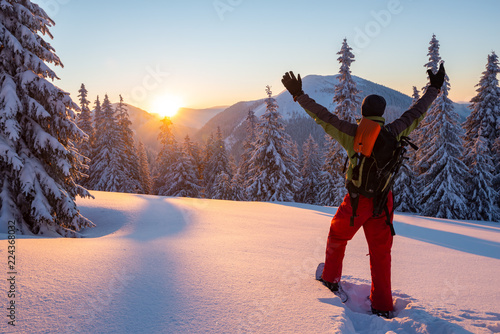 Papiers peints Glisse hiver Adventurer stands with open arms in the winter mountains
