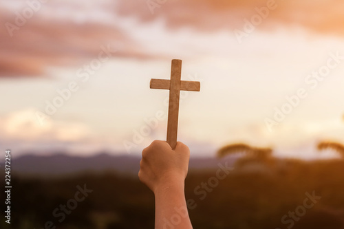 Fotografie, Obraz  human hands praying to the GOD while holding a crucifix symbol with bright sunbe