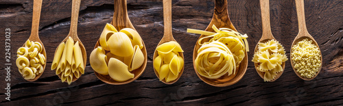 Fotografering Different pasta types in wooden spoons on the table. Top view.