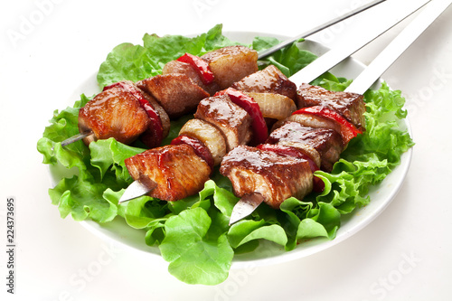 Grilled meat and vegetables over green leaves on white plate.