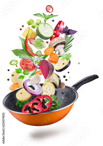 Flying fresh vegetables and spices over a pan. File contains clipping path.