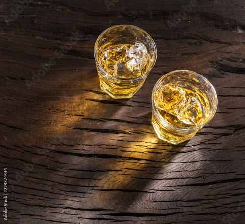 Whiskey glasses or glasses of whiskey with ice cubes on the wooden table. Top view.