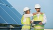 Renewable energy concept. Two energetics employees are walking along a solar construction with a tablet