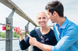Man pointing finger at her girlfriend holding padlock hang on railing