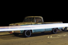 Side View Of A Vintage Classic Pick Up Truck Car And Light Trails Caused By Traffic In Venice, California At Night