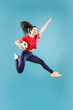 Forward to the victory.The young woman as soccer football player jumping and holding the ball at studio on pink background. Football fan and world championship concept. Human emotions concepts