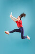 Gadget in modern life. Jump of young woman over pink studio background using laptop or tablet gadget while jumping. Runnin surprised girl in motion or movement. Human emotions and facial expressions