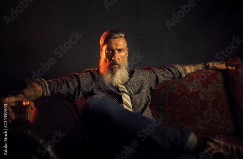 Porträt eines attraktiven, bärtigen, modernen Geschäftsmannes, vor einem dunklen Wallpaper Mural
