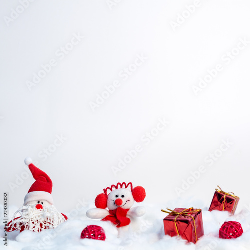 A square white Christmas copy space with red gifts, a plush Santa Claus and a snowman