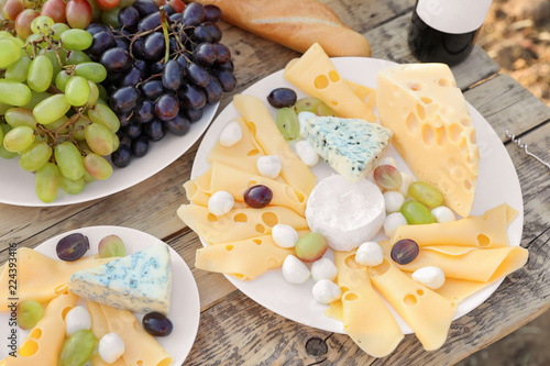 Cheese and grapes on wooden table. Vineyard picnic