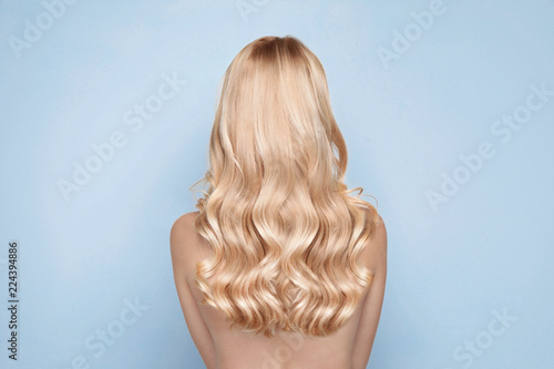 Fotografía  Beautiful woman with healthy long blonde hair on light background