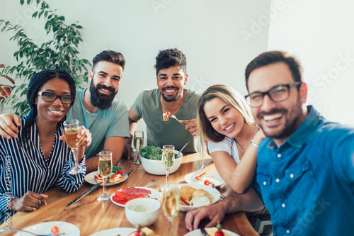 Photographie Group Of Happy Young Friends Enjoying Dinner At Home