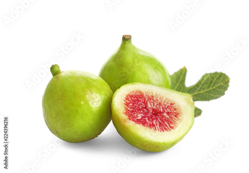 Whole and cut green figs on white background