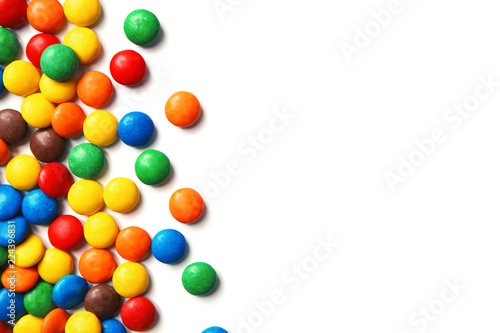 Tasty colorful candies on white background, top view