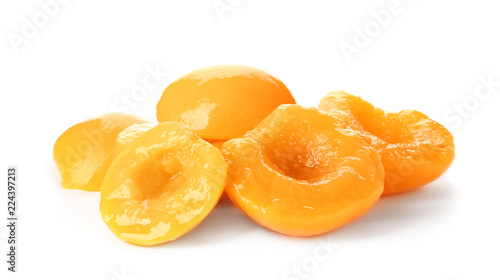 Halves of canned peaches on white background