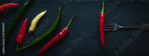 Staande foto Hot chili peppers Mix of chili peppers on dark background, top view