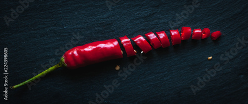 Chopped red chili pepper on dark background, top view