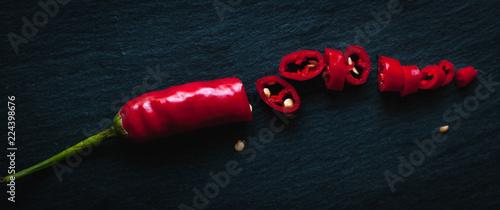 Obraz na płótnie Chopped red chili pepper on dark background, top view