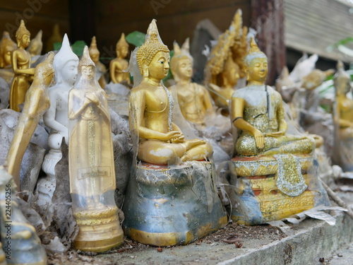 Selective focus of ignored different shapes, styles, and sizes of the buddha statues / images on old spirit house