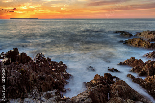 Fotografiet Long exposure seascape with sun setting over Lundy island, from  Woolacombe, Dev