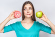 Portrait of dreaming young beautiful girl in blue blouse standing, showing and holding pink donut and green apple in hands with thoughful cunning face on grey background. Indoor,isolated,copy space