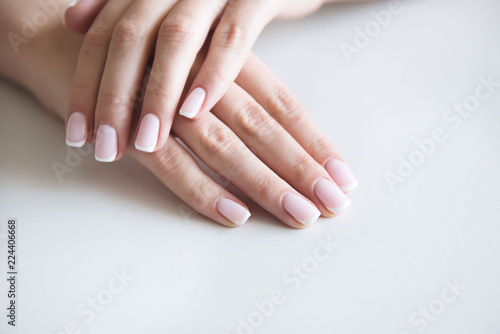 Manicured hands on towel. French manicure.