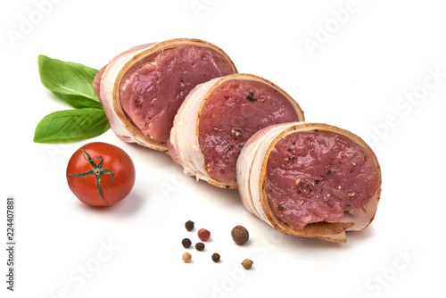 Fotomural Raw Pork medallions wrapped in bacon with basil leaves and peppercorns, isolated on white background