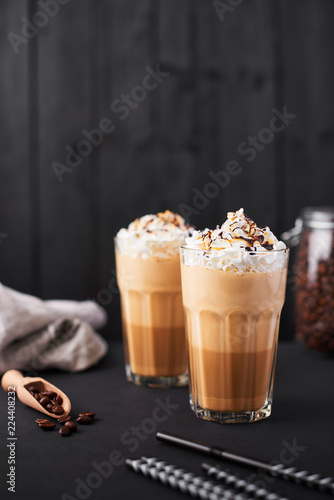 Tableau sur Toile Iced caramel latte coffee in a tall glass with chocolate syrup and whipped cream