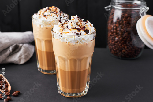 Fotografiet Iced caramel latte coffee in a tall glass with chocolate syrup and whipped cream