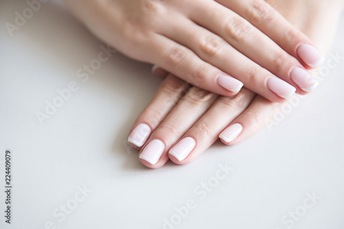 Staande foto Manicure Manicured hands on towel. French manicure.