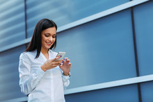 Young Business Woman Reading A Message On The Smartphone Outdoors
