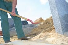 Man Shovelling Sand In Graveyard