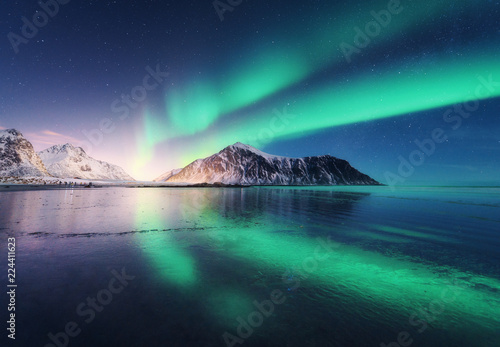 Poster Aurore polaire Northern lights in Lofoten islands, Norway. Green Aurora borealis. Starry sky with polar lights. Night winter landscape with aurora, sea with sky reflection, rocks, beach and snowy mountains. Nature