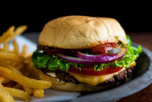 Close Up Of Burger With French Fries Served On Plate