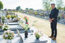 Man Stood Alone Looking At Grave