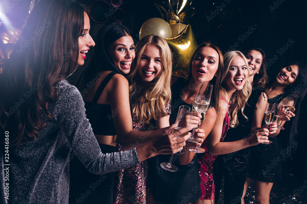 Fototapety, obrazy: Pure celebration. Beautiful young women in evening gown holding champagne glasses and looking at camera with smile while celebrating in nightclub