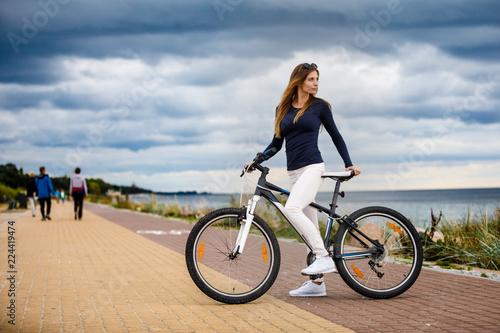 Fototapeta Young woman and bike at seaside obraz na płótnie