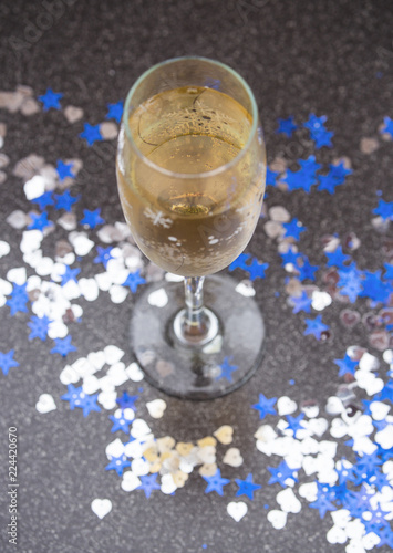 Fotobehang Alcohol Glass of Champagne and Confetti in Form of Stars and Heart. Top View. New Year Consept